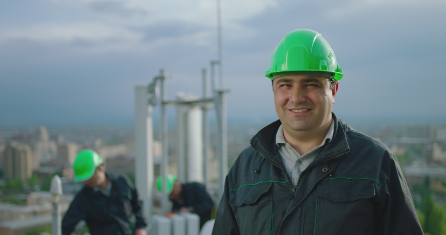 4K Portrait of engineer . Professional telecommunication industry engineer smiling and looking at the camera . Workers wearing safety uniform and hard hat on background with workers and antennas . #1041912355