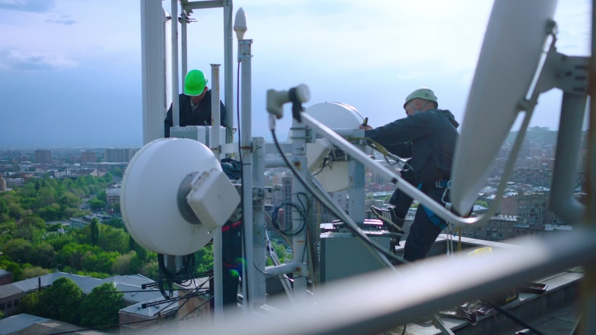 Workers servicing cellular antenna in front of city . Contractors working on a telecommunications mast at height .  Telecommunication technician working on top of cellular antenna. The cell tower. | Shutterstock HD Video #1041919225
