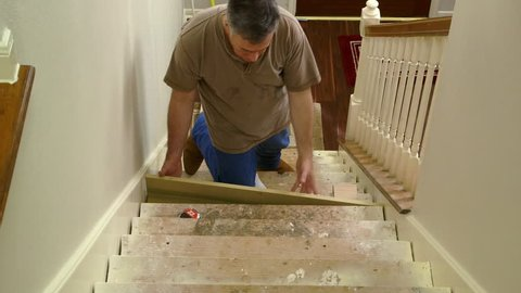 A tradesman or handyman homeowner type fitting in stair riser and measuring for the tread portion of the step.