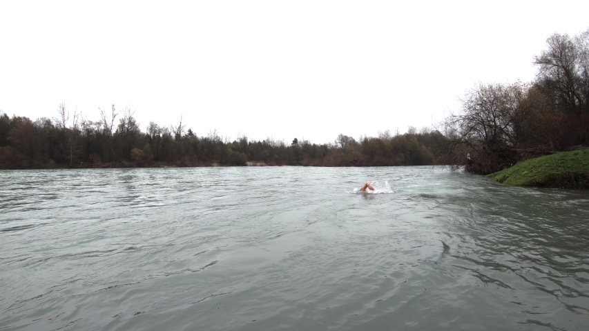 Slow motion athlete man swimming front crawl in cold rapid river | Shutterstock HD Video #1042022125