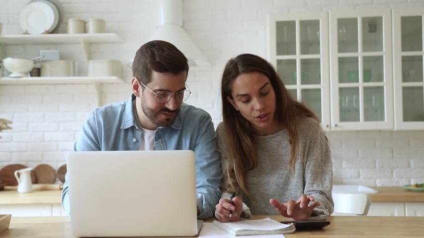 Pleasant focused young mixed race family spouses calculating payments, monthly expenses, using computer banking app. Married couple managing budget, counting bills, doing paperwork together at home. | Shutterstock HD Video #1042155775