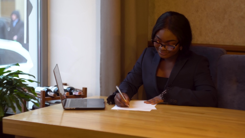 African american businesswoman working with laptop and papers. Busy woman paying bills online banking managing finances checking budget doing paperwork using computer sitting at desk   Shutterstock HD Video #1042268875