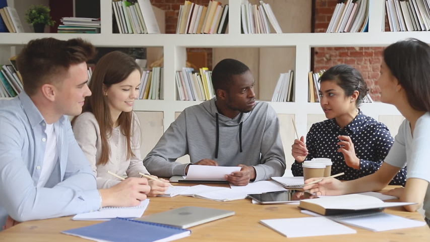 Concentrated mixed race students listening to smart indian female groupmate, explaining educational material. Focused international university friends preparing to college exams together in library.   Shutterstock HD Video #1042308985
