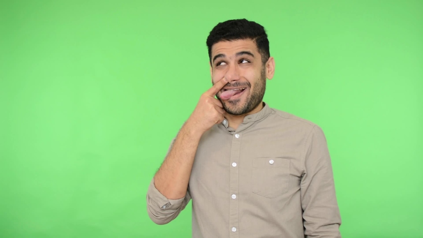 Funny positive brunette man with bristle in shirt picking his nose, pulling out boogers and making stupid grimaces with sticking out tongue, having fun. indoor studio shot green background, chroma key