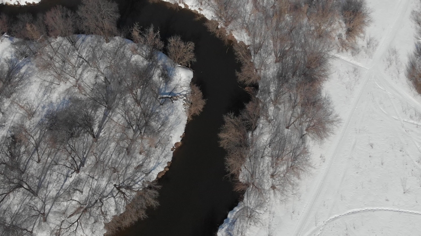 View from the quadrocopter on the river in spring. The river flows among white snow and bare trees | Shutterstock HD Video #1042372705