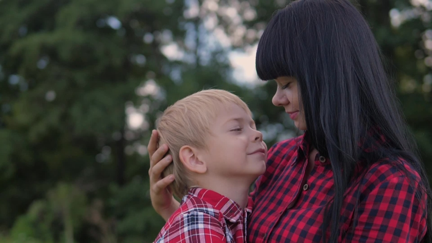 Happy family mom and son concept . mom tender childhood video . slow motion video . mom lifestyle a brunette girl gently hugs takes care of the boy son blonde outdoors | Shutterstock HD Video #1042376065