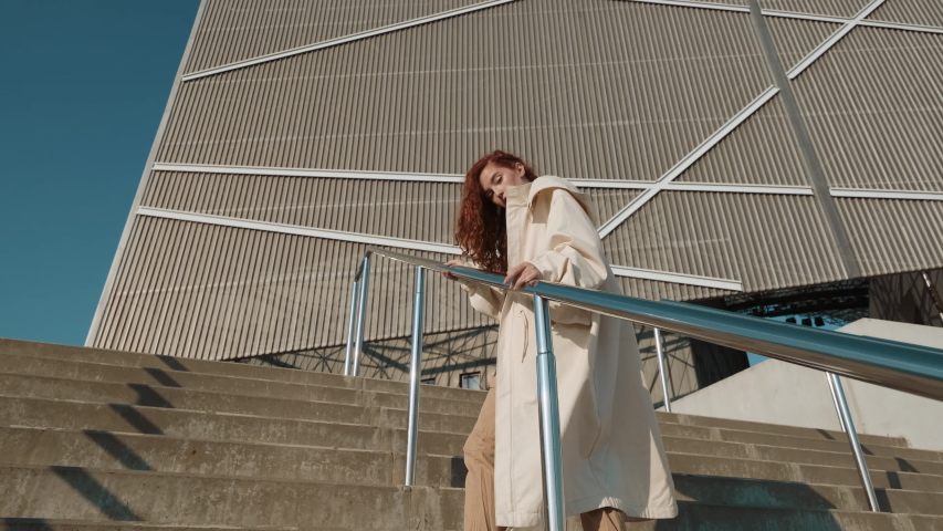Young Red-Haired Girl On The Street. Girl Has Long Curly Hair. Urban Fashion Concept. Girl Walks Up The Stairs Near Modern Building. | Shutterstock HD Video #1042425235