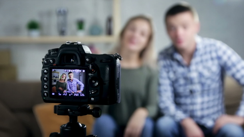 Happy smiling couple sitting on sofa at home embracing looking at camera, young man and woman making video call communicating online or recording vlog together | Shutterstock HD Video #1042437895