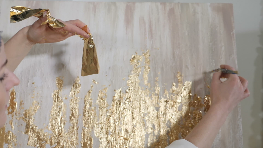 Attractive female artist applying gold leaf to her artwork. Artist decorates picture with tiny sheet of gold. art school, creativity and people concept. Slow motion. Close up. hd | Shutterstock HD Video #1042442485