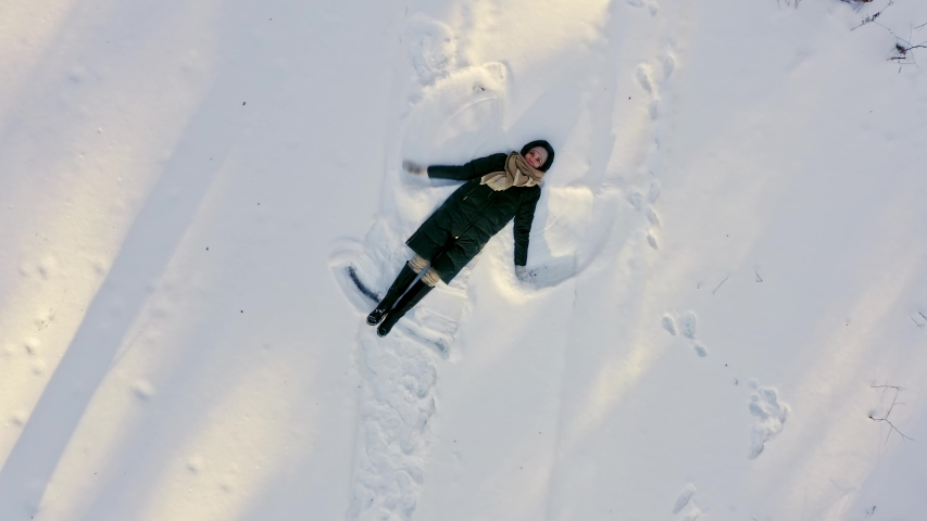 Girl makes snow angel in clearing in the forest, aerial shot. Aerial shoting view of girl happy making by arms snow angel figure and lying in snow. Young woman lying in snow do angles in forest.