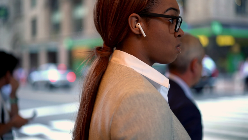 Young dark skinned woman in classic glasses doing crosswalk in city downtown using cellphone device for communicate on way, female in earbuds writing text email connected to 4g wireless  | Shutterstock HD Video #1042487965
