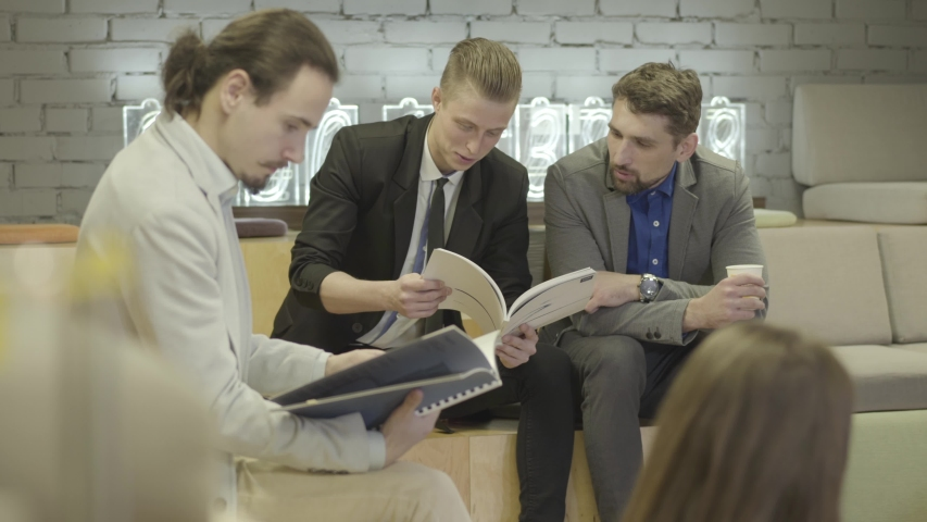Young Caucasian men and women sitting with documents in open space and discussing project. Creative colleagues having brainstorm. Modern lifestyle, coworking, office, business, creativity. | Shutterstock HD Video #1042585105