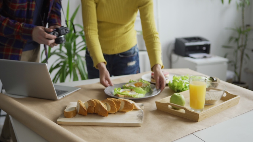 Tilt up of female flatlay stylist arranging objects on table helping young male photographer to take food images, then creative professionals checking pictures on camera | Shutterstock HD Video #1042635475