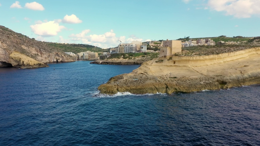 Aerial view of Xlendi tower, beach, bay on Gozo island. Salt pans and sea. Camera moves forward. Malta country