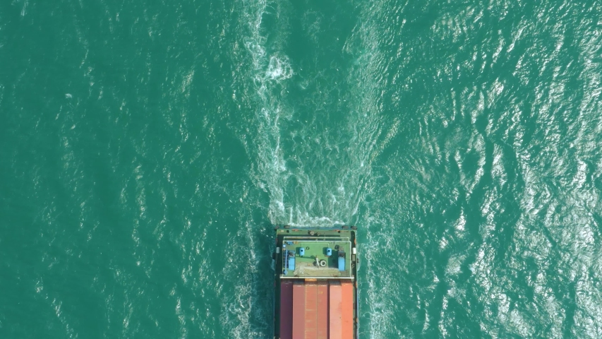 Top down Aerial View of a large container ship sailing at the sea for transporting shipments to other countries   | Shutterstock HD Video #1042656325