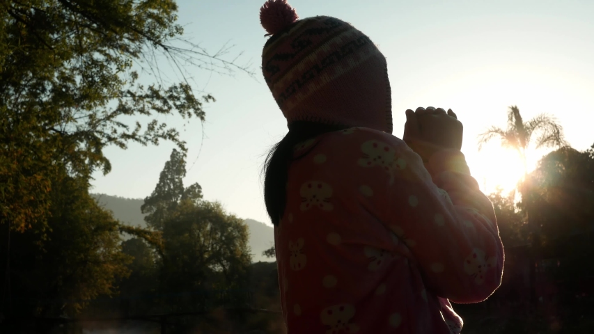 The silhouette of beautiful young woman with raised hands to make a wish with holy things at sunrise background. Spiritual concepts.   Shutterstock HD Video #1042671745