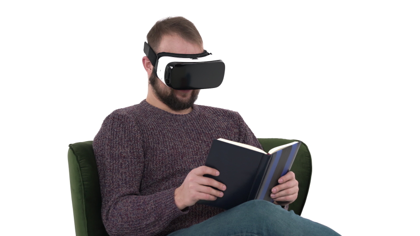 Young hipster man wearing modern high tech VR glasses and checking his notebook. Cool high tech devices usage concept   Shutterstock HD Video #1042778515