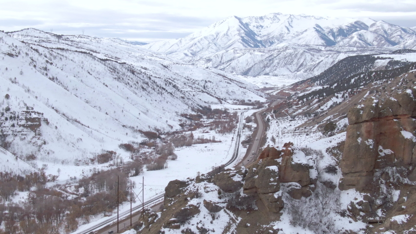 DRONE: Cars and trucks move down a scenic highway leading towards the snowy mountains of Colorado. Spectacular snowy landscape surrounds the scenic interstate freeway crossing the state of Colorado. | Shutterstock HD Video #1042796185