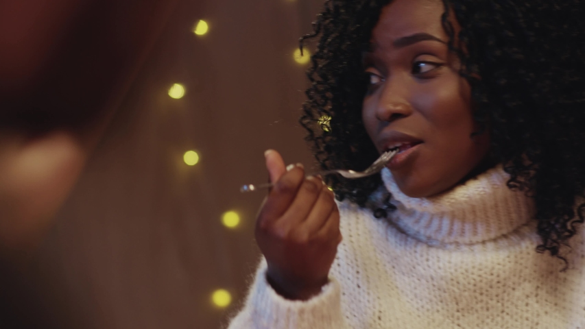 Beautiful black young woman with curly hair eating tasty meals at dinner table communicating with friends having great party holiay celebration on Christmas.   Shutterstock HD Video #1042801345