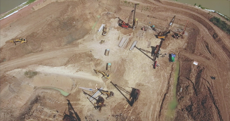 Rising up drone shot of the  construction site. Drilling piles with heavy machinery and excavator loading sand into small trucks  | Shutterstock HD Video #1042809835