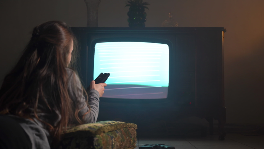 Girl lying on soft old-fashioned textile pillow on the floor in dark mist room and watching retro TV with flicking screen. Woman changing channels with TV remote control, horror atmospere and | Shutterstock HD Video #1043388325