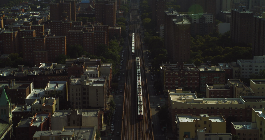 Aerial view city trains, buildings and skyscrapers in New York during the day under blue skies. Wide shot on 4K RED camera.