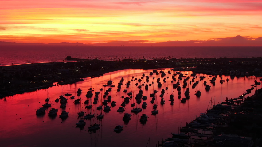Cinematic aerial view of the harbor, ocean and pier in Newport Beach, Orange County in California with boats below during a red and pink sky twilight | Shutterstock HD Video #1043888425