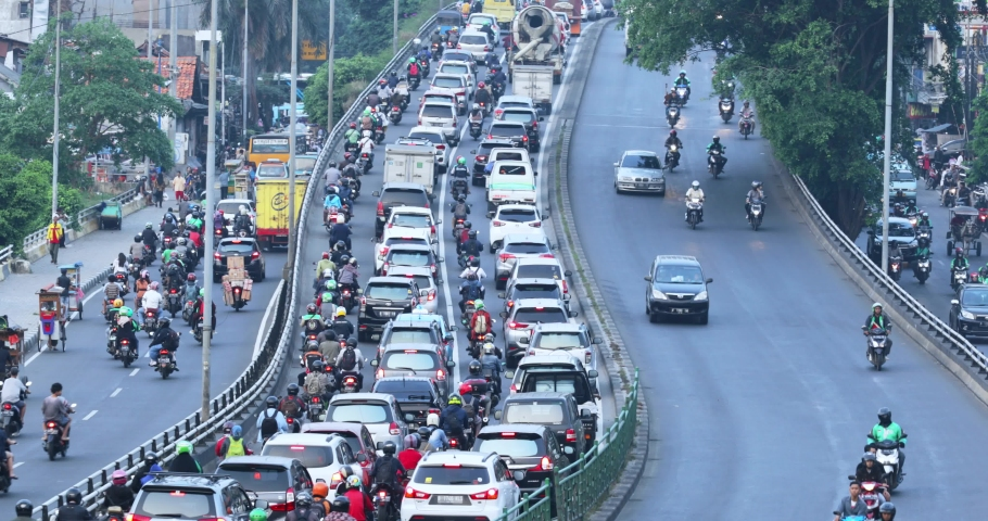 JAKARTA, Indonesia - December 24, 2019: Aerial view of traffic jam in the rush hour with queued motorcycle and cars on road. Shot in 4k resolution