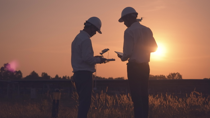 Technician and investor Using Infrared Drone Technology to Inspect Solar Panels and Wind Turbines in Solar cell Farm, Solar cells will be an important renewable energy of the future. | Shutterstock HD Video #1044566755