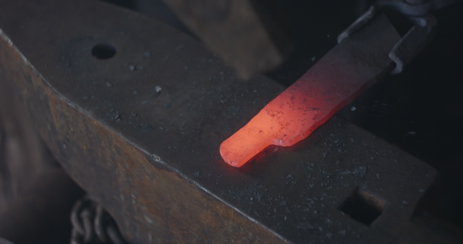 Blacksmith hammering heated iron on ironsmith and making a knife. Slow motion, close up, detail.  | Shutterstock HD Video #1044663295