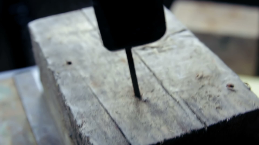 A man hammers a nail into a tree with an old hammer | Shutterstock HD Video #1044756355