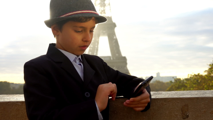 Beautiful boy in a hat is looking on the phone on the background of the Eiffel tower, Paris, France | Shutterstock HD Video #1044774205