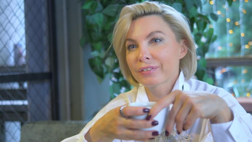 Two beautiful stylish women blondes communicate sitting in a cafe.   Shutterstock HD Video #1044818725