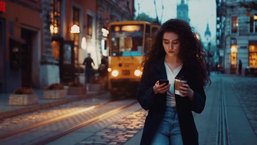 Beautiful young caucasian brunette curly haired woman walking along the street uses phone texting drinks coffee in city at night Warm spring or autumn evening business outdoor lifestyle city lights   Shutterstock HD Video #1044839305