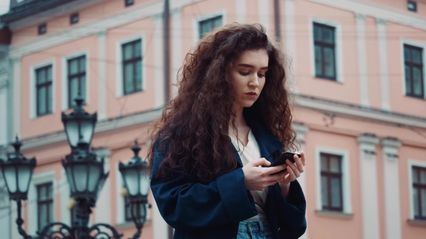 Caucasian young curly hair woman in a black coat uses phone walk in the city center looks around smile happy summer internet business outside technology eye spring mobile slow motion   Shutterstock HD Video #1044839335