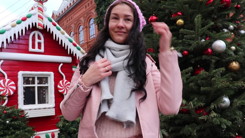 Portrait of a happy young woman on the background of Christmas winter decorations in the street   Shutterstock HD Video #1044892045