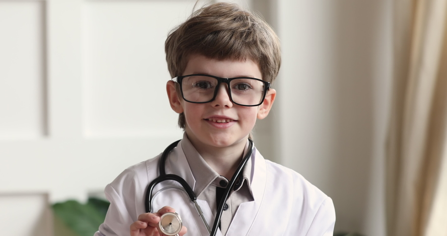 Happy funny adorable cute little preschool child boy wear white medical coat glasses holding stethoscope looking at camera playing doctor alone, children future professions concept, closeup portrait