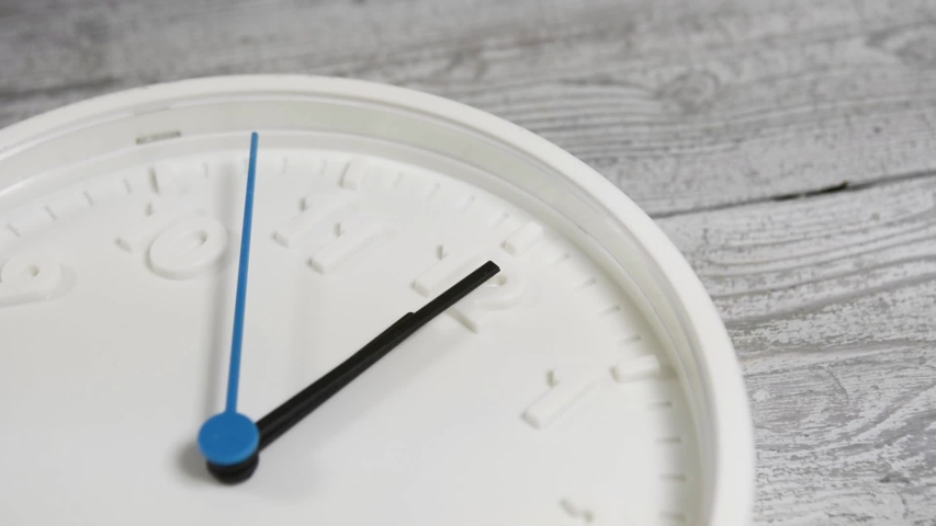 White clock on wooden surface.  Moving blue second hand   Shutterstock HD Video #1044955255