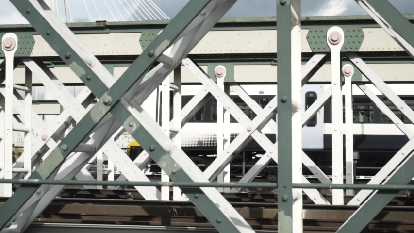 Close-up view of the white wagon going rapidly on the bridge against the blue sky. Action. Urban rail transport | Shutterstock HD Video #1044988735
