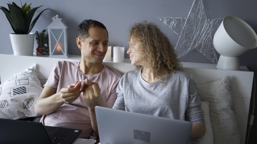 Couple in pajamas using laptop at morning time in modern bedroom. Man and woman caress and kissing in bed enjoying togetherness while working on notebook, browsing or online shopping | Shutterstock HD Video #1044998035