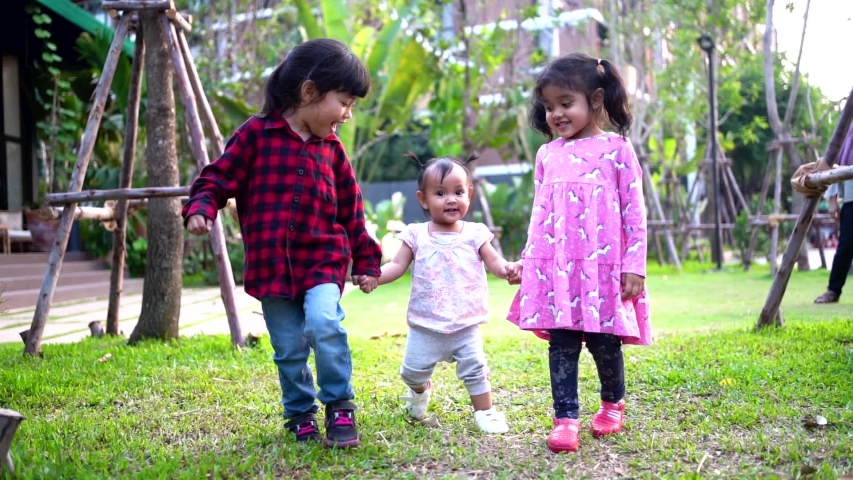 Little cute sisters is holding hand together and walking together in the garden. Two elder sister is teaching the little sister to walk. Happy family concept. (Slow motion video) | Shutterstock HD Video #1045005355