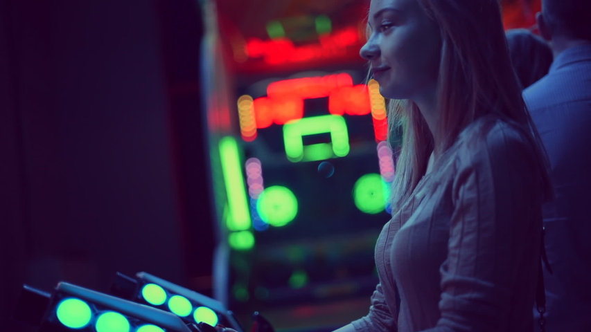 Close up portrait of a beautiful excited caucasian girl watching an action video on a computer. Play vintage game, slot machine. She has blonde hair. Screen adds reflections to her face | Shutterstock HD Video #1045088185