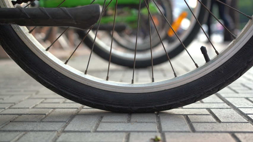 Bicycle wheels on footpath with pedestrian walking | Shutterstock HD Video #1045089835