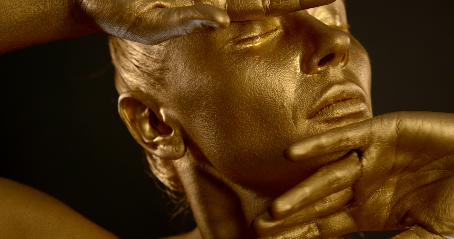 Attractive lady face and fingers covered with golden paint | Shutterstock HD Video #1045105135