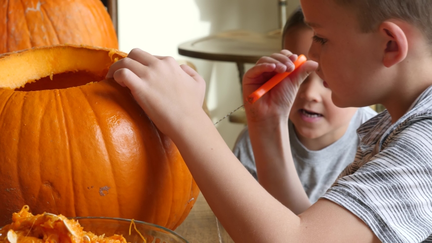 A family carving pumpkins for halloween at the kitchen table in their house | Shutterstock HD Video #1045115365
