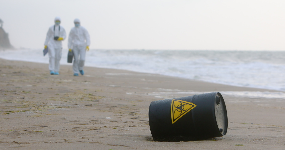 Two men in white protective suits are approaching a black barrel with a sign of biological danger, that lies on the seashore. | Shutterstock HD Video #1045183075