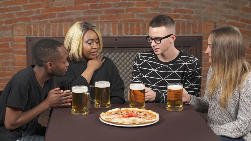 Close-up of Afro American and Caucasian couples communicating in pub. Multi-racial friendship concept | Shutterstock HD Video #1045187035