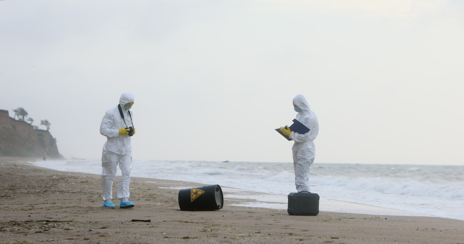Two men in white protective suits are inspecting the seashore, where a black barrel with a sign of biological danger lies. | Shutterstock HD Video #1045209235