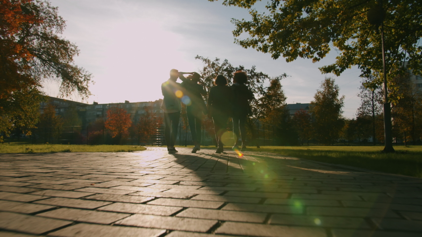 Back view of male and female friends walking outdoors in city doing high-five laughing having fun together. Communication, friendship and lifestyle concept. | Shutterstock HD Video #1045402195