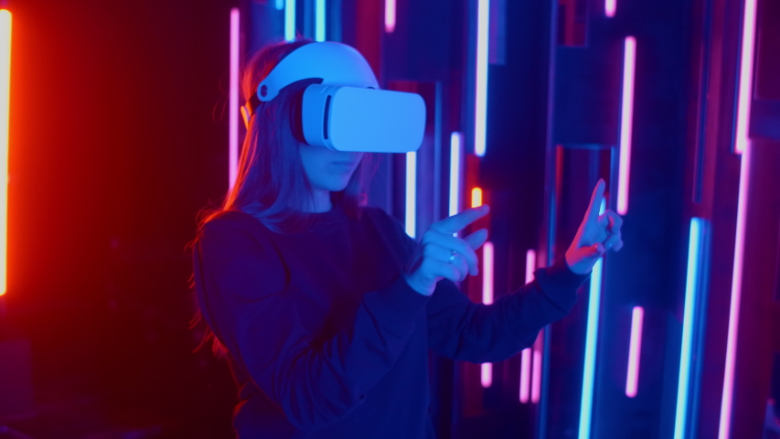Faceless woman wearing VR headset in dark space with neon light lamps, user turning head side to side looking virtual reality, shoting through colored flares and bokeh on foreground.   Shutterstock HD Video #1045442515